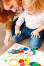 Cute little redhead girl painting with brush Royalty Free Stock Photography