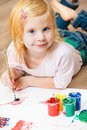 Cute little redhead girl painting with brush Stock Images