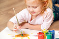 Cute little redhead girl painting with brush Royalty Free Stock Photos