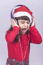 Cute little santa girl listening to music dressed up as screaming while Royalty Free Stock Image