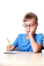 Cute little schoolboy wearing glasses sits at a ta young funny child table writing in notepad with pencil and thinking Stock Photos