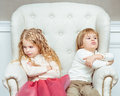 Cute little siblings boy and girl being at odds with each othe other sitting on armchair Stock Image