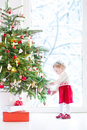 Cute little toddler girl decorating christmas tree wearing a red festive dress Royalty Free Stock Photography