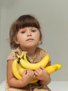 Cute little toddler girl holding a bananas Royalty Free Stock Photo