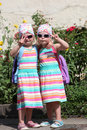 Cute little twin girls making v signs dressed in identical dresses and headscarves and wearing sunglasses standing in the sunshine Stock Images
