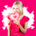 Cute love hungry girl eating big red heart adorable blond winking while biting into a valentine eat your out concept Royalty Free Stock Photo