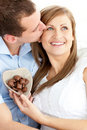 Cute man kissing his girlfriend holding chocolates Royalty Free Stock Image