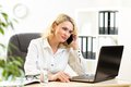 Cute middle aged business woman working in office businesswoman lady talking on mobile phone and looking at laptop Stock Photo