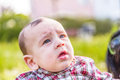 Cute months baby gaping old with light brown hair in red checkered shirt and beige pants is Royalty Free Stock Photo