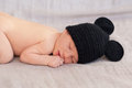 Cute newborn baby in black mouse hat soft image of sleeping on grey background focus on face and hand Royalty Free Stock Image
