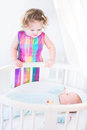 Cute newborn baby boy looking at his toddler sister standing next to white bed Stock Images