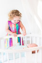 Cute newborn baby boy looking at his toddler sister standing round crib Royalty Free Stock Photos