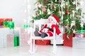 Cute newborn baby boy in santa costume under christmas tree sitting a Stock Image