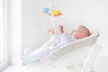 Cute newborn baby boy watching colorful mobile toy Royalty Free Stock Photo
