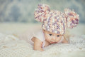 Cute newborn baby girl in knitted cap with bubonic portrait of a little a hat lying on white fluffy bed Stock Image