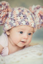 Cute newborn baby girl in knitted cap with bubonic portrait of a little a hat lying on white fluffy bed Stock Photos