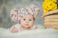 Cute newborn baby girl in knitted cap with bubonic portrait of a little a hat lying on white fluffy bed Royalty Free Stock Image