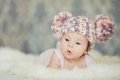 Cute newborn baby girl in knitted cap with bubonic portrait of a little a hat lying on white fluffy bed Royalty Free Stock Images