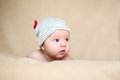 Cute newborn girl in grey cap with red horns Stock Images