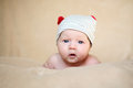 Cute newborn girl in grey cap with red horns Royalty Free Stock Image