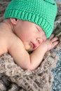 Cute newborn headshot portrait of adorable baby boy week old sleeping on his belly and wearing a colourful green beanie Stock Photo