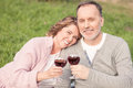 Cute old married couple is enjoying drink in park pretty mature husband and wife are celebrating their anniversary they are Royalty Free Stock Photo