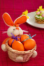 Cute orange bunny basket easter eggs red mat Royalty Free Stock Photo