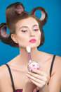 Cute pin up girl applying blusher in curlers Stock Photo