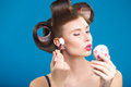 Cute pin up girl applying blusher in curlers Royalty Free Stock Photography