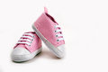 Cute pink baby girl sneakers close up on gray Royalty Free Stock Photo