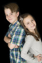 Cute portrait of boy and girl standing back to back smiling Royalty Free Stock Photo