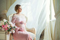 Cute pregnant woman sitting on chair near billowing curtains and hugs belly with love Royalty Free Stock Photo