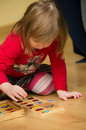 Cute preschool girl playing picture dominoes floor Royalty Free Stock Photos