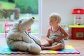 Cute preschooler girl playing doctor game with her toys happy child adorable blonde toddler teddy bear sitting comfortable on the Royalty Free Stock Photos