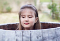 Cute pretty young girl hiding in a barrel with downcast eyes outdoors with just her head protruding Royalty Free Stock Image