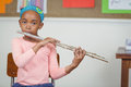 Cute pupil playing flute in a classroom portrait of school Stock Image