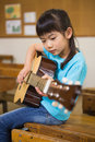Cute pupil playing the guitar at elementary school Royalty Free Stock Photo