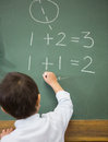 Cute pupil writing maths on chalkboard at the elementary school Stock Images