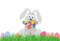 Cute rabbit with a bouquet of Easter eggs. A hare with flowers sits on the grass.