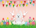 Cute rabbit with easter bunnies on a stick with red bows. The hare sits
