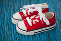 Cute red baby sneakers on wooden blue background Royalty Free Stock Images