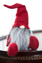 Cute red christmas santa elf and white made of fabric sitting on a dark wood table wearing a hat with only his nose and long grey Royalty Free Stock Photography
