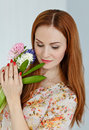 Cute red-haired girl holding flowers and smiling, close-up