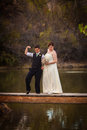 Cute same sex couple on dock macho lesbian groom with bride over pond Royalty Free Stock Photo