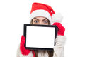 Cute santa girl hiding behind tablet computer young caucasian wearing beanie hat and red gloves with blank screen copy space Royalty Free Stock Photo