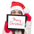 Cute santa girl hiding behind tablet computer young caucasian woman with hat with merry christmas text on screen isolated on white Stock Photography