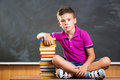 Cute school boy sitting with books in classroom against blackboard Stock Photo