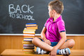 Cute school boy sitting with books in classroom against blackboard Stock Image