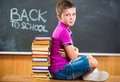 Cute school boy sitting with books in classroom against blackboard Stock Images