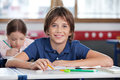 Cute schoolboy smiling in classroom portrait of with classmate studying background at Stock Image